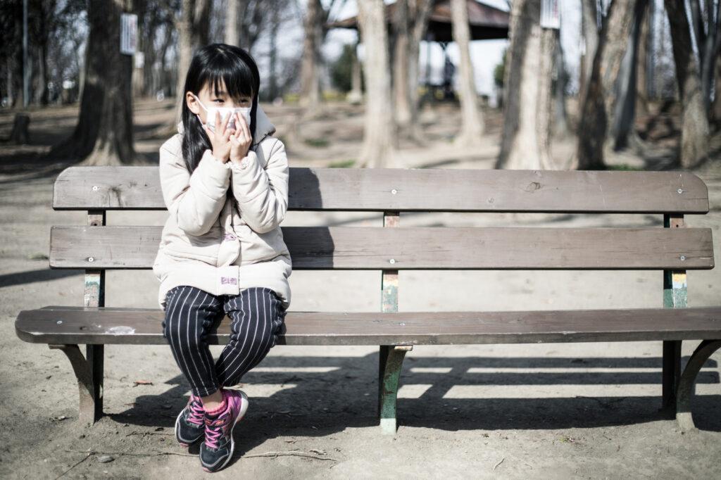 マスクをして座っている女の子