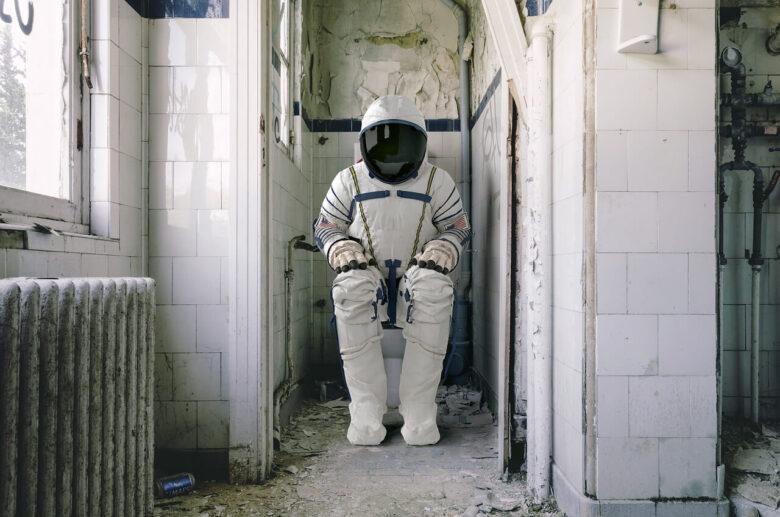 トイレに入る宇宙飛行士